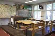 Vor Schiefertafel und Landkarte sitzt der Lehrer